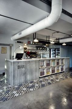 using a patterned tile around the base of this bar area helps to give a zonal feeling to the space. the unfinished ceiling and view of the services along with the concrete surfaces help to create a construction type atmosphere.