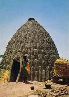 Africa | Musgum woman standing in front of her traditionally built home (made from compressed sun dried mud). Far north province in cameroon || Scanned postcard.