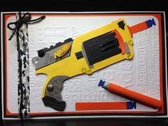 """Birthday card made for nephew Jalen on his 11th birthday who is super into Nerf guns. Copied picture of gun from online, cut pieces of colored card stock and assembled; mounted on cardboard. Forgot to cut hole and attach the gun's trigger. Rolled up and inserted a $20 bill into a dimensional nerf dart, which is attachable/detachable to the card using Velcro (have since discovered """"Scotch Restickable Tabs"""" that are double-sides adhesives that remove easily and clearly). Ranger """"Glossy…"""