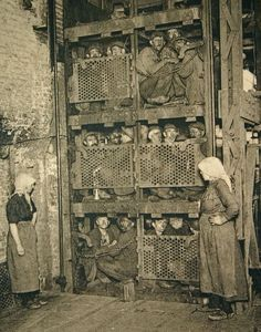 Crammed into a coal mine elevator, coming up after a day of work.  They aren't even standing up.