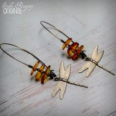 Celebrating all things Outlander! These earrings are some of my pieces in honor of Diana Gabaldons epic book series about Jamie and Claire (of which I am a huge fan)! Natural gemstone quality Baltic Amber is carefully wrapped with my signature wire wrap, both for beauty and for security. A stylized dragonfly dangles gently from Baltic Amber gemstone beads. These earrings are about 3 inches long, and are closed with kidney ear hooks that close so you will never accidentally loose one of these…