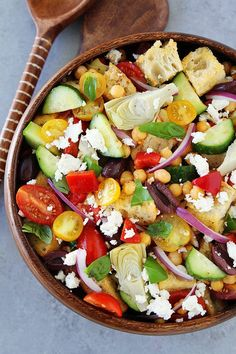 Greek Panzanella Salad made with cubes of crusty bread, tomatoes, cucumbers, chickpeas, artichoke hearts, peppers, olives, red onion, feta cheese, and a simple Greek salad dressing.