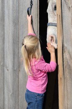 girl putting her horse away and shutting the barn door, little four year old child.