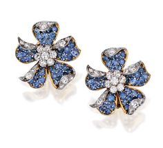 PAIR OF TWO-COLOR GOLD, SAPPHIRE AND DIAMOND EARCLIPS Designed as flowerheads set with round diamonds weighing approximately 1.75 carats, the petals decorated with 47 round sapphires, gross weight approximately 18 dwts, signed Van Cleef & Arpels.
