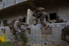 U.S. Marines with Company E, Battalion Landing Team 2nd Battalion, 4th Marines, (BLT) 31st Marine Expeditionary Unit, jump over a wall while conducting a vertical assault at Combat Town, Okinawa, Japan, Dec. 8, 2014. Company E is conducting training as part of the MEU Exercise and pre-deployment training. (U.S. Marine Corps Photo by Lance Cpl. Richard Currier/ Released)