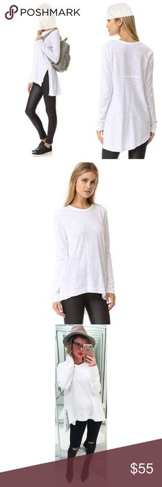 Wilt White Asymmetrical Cotton Tunic A slit relaxes the raw, uneven hem on this loose-cut Wilt tee. Ribbing traces the crew neckline. Long sleeves. Faint spot above the back hem as pictured, otherwise spotless.  Fabric: Slubbed jersey. 100% cotton. Wash cold. Made in the USA. Length 1: 24in, from front shoulder Length 2: 28in, from back shoulder Wilt Tops Tunics