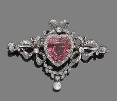 A tourmaline and diamond brooch  The heart-shaped pink tourmaline, within an old brilliant, single and rose-cut diamond ribbon and garland surround, old brilliant and single-cut diamonds approx. 0.30ct total, length 3.9cm, fitted case by Tessier, New Bond Street. Edwardian or Edwardian style or earlier.