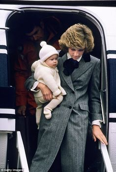 Pictured, Diana, Princess of Wales carries her son, Prince Harry, off a flight at Aberdeen Airport