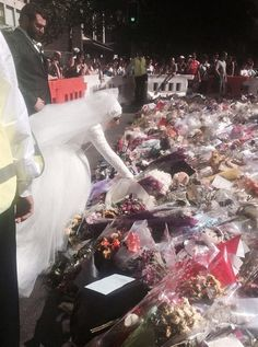"""As the memorial to the victims of the Sydney siege continues to grow, a Muslim bride has made a pilgrimage on her wedding day to lay flowers at Martin Place. Adorned in a white wedding dress, which included a traditional white hijab and veil, newlywed Manal Kassem arrived at the memorial with her husband, Mahmod Homaisi, to place her wedding bouquet among the tens of thousands of other floral tributes in the square."""