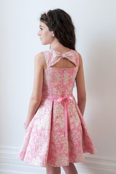 Presenting this pink dream prom dress for girls from David Charles' latest collection. Pair a soft shade of pink with a contrasting floral print and the result is this truly elegant prom dress. Whether your girl needs a dress to make a statement this spring, or you're looking for a birthday gift idea for her, you'll love the retro meets contemporary style of our evening dresses. This wardrobe staple includes a delicate pearl waist belt which transforms into a pink satin ribbon at the back…
