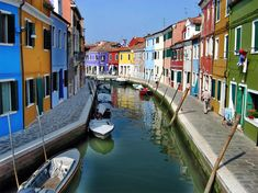 burano, venice, italy. houses along the canal with boats.    loved burano, can't wait to go to venice in the fall.