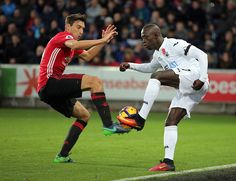 Modou Barrow of Swansea City is challenged by Matteo Darmian of Manchester City during the Premier League match between Swansea City and Manchester...