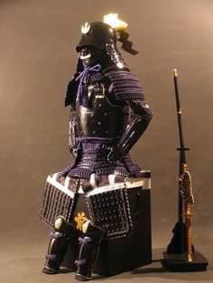 Armour with a hishinui-do, kebiki-laced sode and kusazuri, and zunari kabuto.  Styling appears to be Momoyama period, but likely a modern reproduction.  Not sure about the rear datamono - I've never seen one like it.