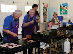 """Noreen Roberts, right, a volunteer for the Vulcan Flying Club, had some help from some Vulcan Lions Club members in preparing the meal at the 25th annual Fly in Breakfast at the Vulcan Airport on July 15. From left, Lions Club President Del Olsen, Secretary Emmett Meehan, who waved """"hello"""" with his spatula, and Lions member Richard DeBolt. Giselle Wedemire, Vulcan Advocate"""