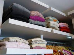 As malhas foram colocadas em prateleiras altas, pois são usadas apenas no inverno. Elas são organizadas de acordo com as golas - das abertas para as fechadas, e depois por cor.