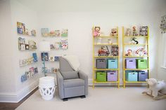 Love the pops of color of the library wall and shelves against this white, serene #nursery!