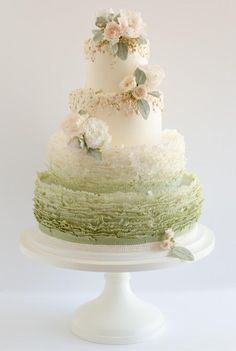 Stunning Maggie Austin Wedding Cake with the bottom two tiers being ruffled and ombre green.  Cascading flowers with pink bring the entire creation into a work of art by another master.  Gorgeous!   ᘡղbᘠ