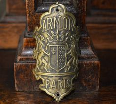 "Antique French Brass Bicycle Headbadge Armor Paris with Lions Shield Crest and Crown Design Measures 1 1/2"" x 3 1/16"" In Antique As Found Condition 2 Mounting Holes"