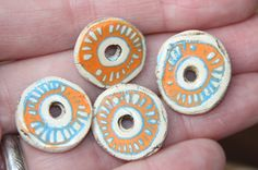 A pair of orange and blue and natural and rustic earthy ceramic disc beads connectors; nr. B94