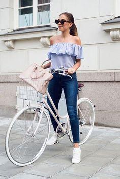 Blusa com decote ombro a ombro e babado, calça jeans, tênis branco.