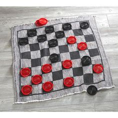 """Play a larger than life match with our Jumbo Checkers Floor Mat. Each set comes with oversized 3"""" game pieces and a cotton rug (good luck misplacing any of the pieces)."""