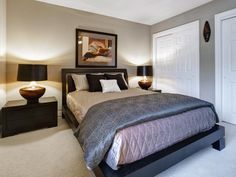 A black contemporary platform bed is the main character in this gray bedroom with soft lighting. Dark nightstands topped with matching lamps flank the bed.