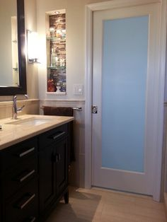 Frosted glass pocket door allowed more light to enter the small bathroom and made the space look bigger.