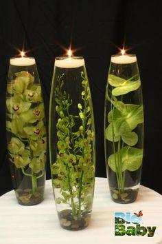 Llena vasos o jarrones con agua, ponle piedras en el fondo, una planta de tallo largo y arriba una veladora.