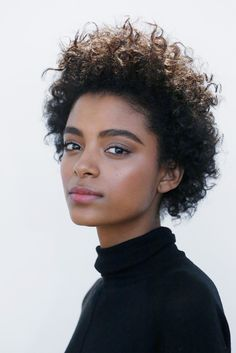Natural curly hair with a lightly groomed brow, rose blush and pink lip.