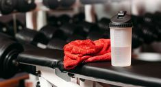 Sport, fitness, healthy lifestyle and bodybuilding concept - close up of bottle with water and wet towel in gym background.  Set of personal sport stuff lay on training  bench in fitness gym ** Note: Shallow depth of field