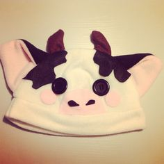 A cow beanie/plushy hat! It's made out of soft, kind of stretchy polar fleece! The blush marks, horns, patches, nose and nostrils are made out of felt, and is securely hot glued on or sewn in. The eyes are black buttons, and are also securely affixed with hot glue.    The hat would fit on a head ...