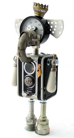 """Bambaloots"" Height: 13"" Principal Components: Pressure gauge, camera, screen door closer, oil lamp burner, bolo tie tips, vegetable steamer fins, faucet handles, hose fittings All Fobots have a heart inside, and you can see his through the top lens of the camera"