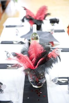 Hand made center pieces, rose bowls, filled with black sand or black rocks, dice & poker chips placed along the edges of the vase underneath the black rocks or sand, and red & black ostrich feathers