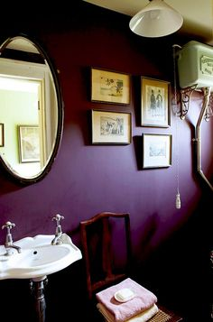 Plum purple powder room with framed vintage inspired artwork.