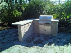 Built-in grill on paver patio by Bahler Brothers with space to pull up bar stools.