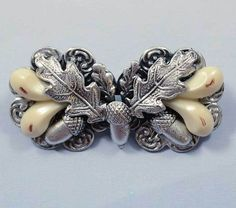 "Vintage Czech Folklore Brooch.This brooch belongs to a type of traditional jewellery called `Trachtenschmuck' (German for `folk costume jewellery'). These pieces were - and are still - commonly used in Bavaria, Austria etc.  This particular brooch has silver plated naturalistic acorns and oak leaves, and the `stones' are of plastic but they would normally be canine teeth of deer, called ""Grandeln"" in German! These are hunting trophies and are used both in women's and men's jewelery."