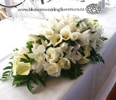 Wedding reception head bridal table flower arrangement in a long and low styles with white and cream roses, calla lilies, orchids and tulips.