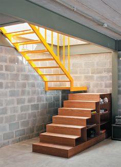 A escada desenhada pelo arquiteto foi executada em duas partes. A primeira, fabricada com freijó pela M3 Marcenaria, também funciona como estante dos dois lados.
