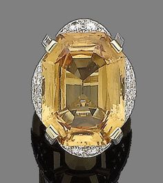 A topaz and diamond dress ring  The cut-cornered step-cut topaz, to a gallery set with brilliant-cut diamonds accented by corners of baguette-cut diamonds, diamonds approx. 2.60cts total, numbered, ring size H, cased by Cartier