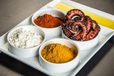 """At the Chicago restaurant Baume & Brix, octopus is grilled and served """"Fun Dip-style."""" This means that it's laid out in a small bowl with a strip of olive oil on the side. Guests are instructed to dip the octopus into the oil, then dunk it into Peruvian yellow chili powder, coconut powder, or smoked-paprika-tomato powder."""