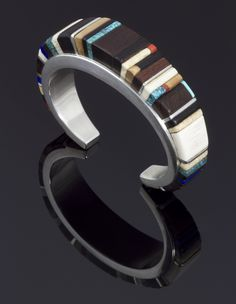 Cuff | Charles Loloma. Sterling silver,  inlayed with ironwood, fossil ivory, Lone Mountain turquoise, coral, and lapis