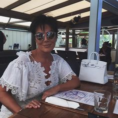 Kardashian Outfits in St. Barts | POPSUGAR Fashion - Kris Jenner Completed Her Breezy White Cover-Up With the Perfect Accessories - Her tiny white Hermès satchel and mirrored aviators helped her achieve a casual yet polished look.