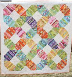Rainbow Connection Quilt by amy smart, via Flickr.  I love how all these bright, busy prints look against the white background fabric.  Must buy some white fabric!!