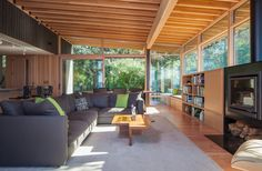 Contemporary Living Room with Built-in bookshelf, Window seat, Wood Stove fireplace, Exposed beam, sliding glass door, Paint