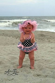 Cutie on the beach in her pink and black bathing suit.  Adorable