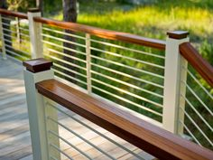 Sustainable mahogany wood railing caps lend elegance to the nautical-style, powder-coated aluminum rail system.