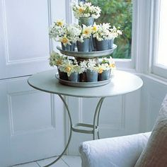 Build a beautiful table display - carefully place trays on top of each other, balanced with an upturned flowerpot, and surround with small zinc flowerpots filled with spring flowers.