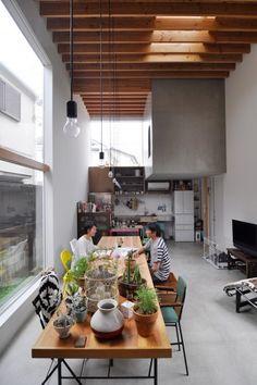 天井高は5m。上に飛び出たボリュームは、姉夫婦のキッチンの一部。テーブルは以前の家の梁をリサイクルしてつくったもの。