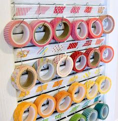 Upcycled SHUTTER to organize WASHI TAPES and large bent paperclips for the hooks.  Love the strip of tape sample above each one to brighten it up even more.
