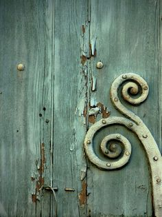 Old door with beautiful pealing paint and celadon metal embellishment.